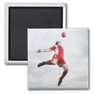 Soccer player and soccer ball in mid-air 2 inch square magnet