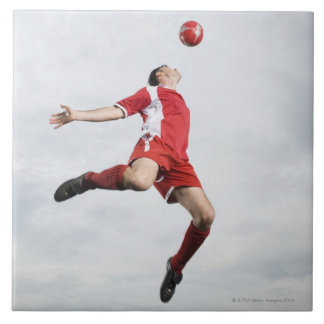 Soccer player and soccer ball in mid-air ceramic tile