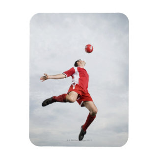 Soccer player and soccer ball in mid-air rectangular photo magnet
