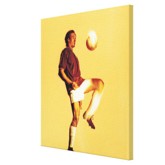 soccer player bouncing ball off knee canvas print