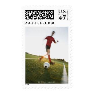 Soccer player dribbling ball postage