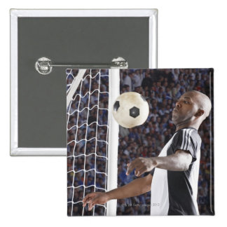 Soccer player facing mid air ball in goal mouth pin