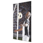 Soccer player facing mid air ball in goal mouth canvas print