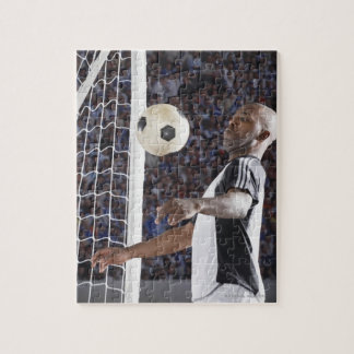 Soccer player facing mid air ball in goal mouth jigsaw puzzle