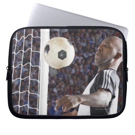 Soccer player facing mid air ball in goal mouth laptop sleeves