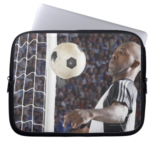 Soccer player facing mid air ball in goal mouth laptop sleeve