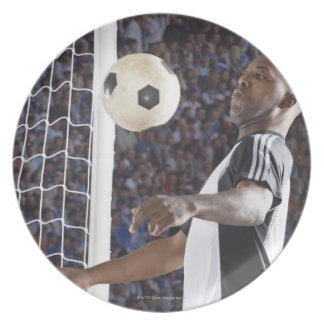 Soccer player facing mid air ball in goal mouth plates