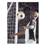 Soccer player facing mid air ball in goal mouth postcard