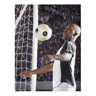 Soccer player facing mid air ball in goal mouth postcards