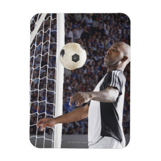 Soccer player facing mid air ball in goal mouth rectangular photo magnet