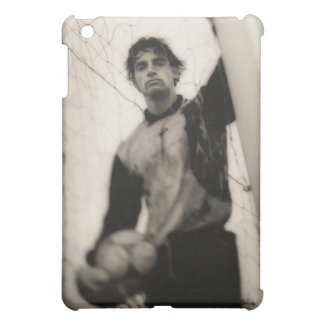 Soccer player standing behind net iPad mini cases