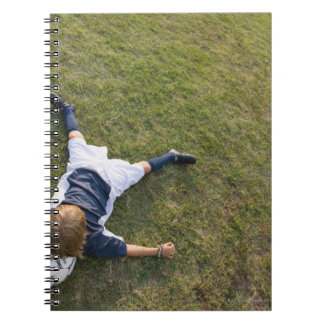 Soccer player with head on football note book
