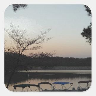 Sol poniente, luna de levantamiento sobre punta de pegatina cuadrada