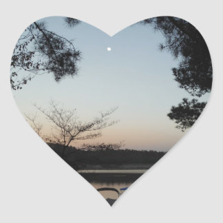 Sol poniente, luna de levantamiento sobre punta de pegatina en forma de corazón