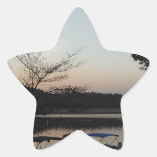 Sol poniente, luna de levantamiento sobre punta de pegatina en forma de estrella