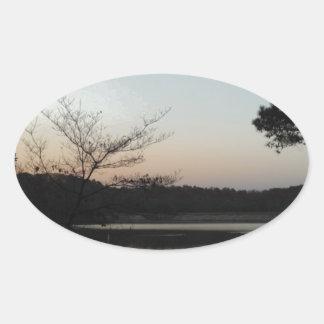 Sol poniente, luna de levantamiento sobre punta de pegatina ovalada