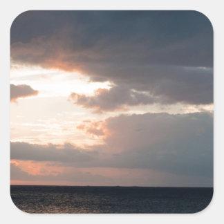 Sol poniente sobre el océano pegatina cuadrada