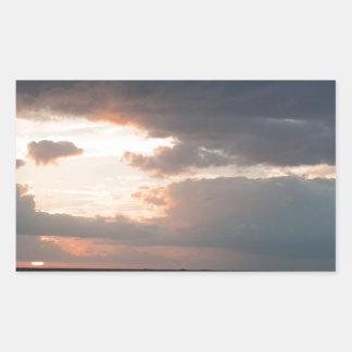 Sol poniente sobre el océano pegatina rectangular