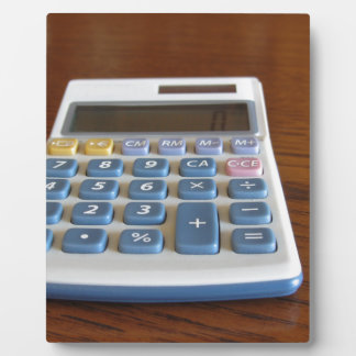 Solar calculator on a wooden table plaque