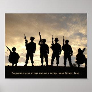Soldados en silueta de la patrulla contra el cielo póster