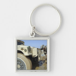 Soldier unties a rope to tow a humvee keychain