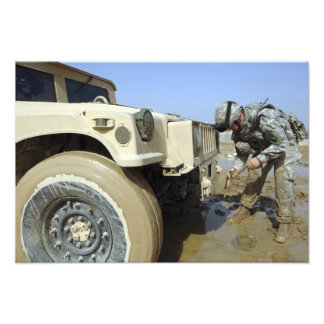 Soldier unties a rope to tow a humvee photo print