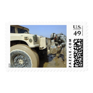 Soldier unties a rope to tow a humvee postage