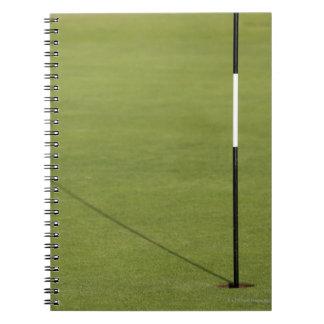 sombra de la bandera del golf en verde del campo libreta espiral