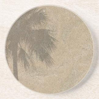 Sombra de la palmera en el fondo de la arena de la posavasos para bebidas