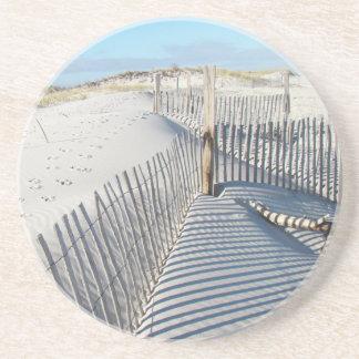 Sombras, dunas de arena, y cercas posavaso para bebida