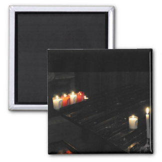 Some religious candles on a black support in a chu 2 inch square magnet