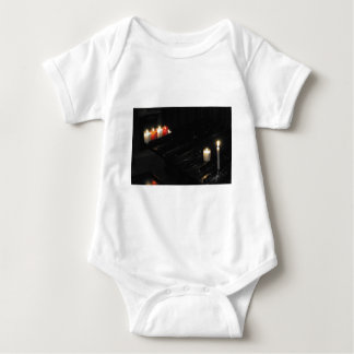 Some religious candles on a black support in a chu baby bodysuit