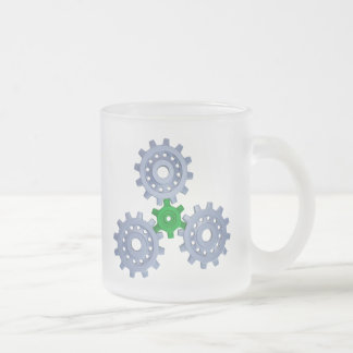 Some silver gears with a little green frosted glass coffee mug