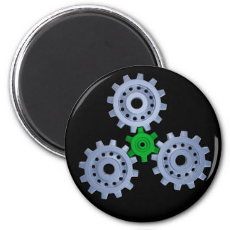 Some silver gears with a little green refrigerator magnet