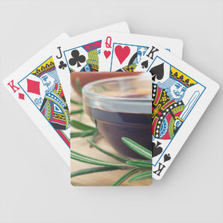 Soy sauce in a glass and a sprig of rosemary bicycle playing cards
