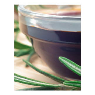 Soy sauce in a glass and a sprig of rosemary letterhead