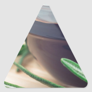 Soy sauce in a glass and a sprig of rosemary triangle sticker