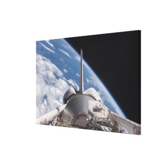 Space Shuttle Discovery backdropped by Earth Canvas Print