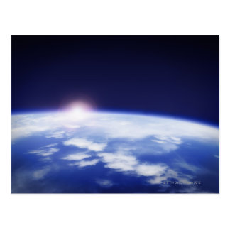 Space with rising sun above planet earth post card