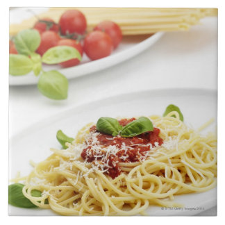 Spaghetti with tomato sauce and basil tiles