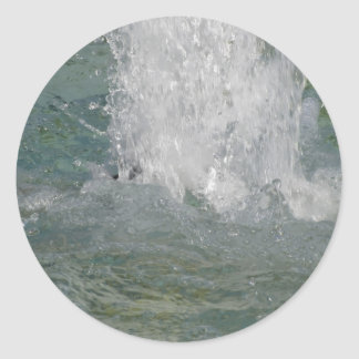 Splashes of fountain water in a sunny day classic round sticker