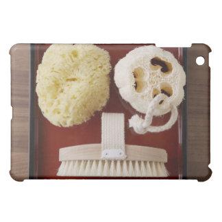Sponge, loofah, brush on red tray iPad mini covers