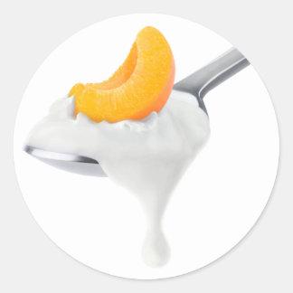 Spoon of peach or apricot yogurt classic round sticker