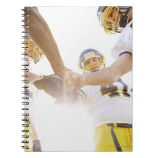 sportsmen standing with hands together notebook