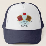"""SPREAD THE LOVE TRUCKER HAT<br><div class=""""desc"""">Peanut butter and jelly sandwich holding hands with heart on top telling to spread the love.</div>"""