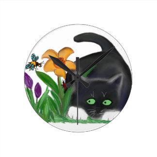 Spring Flower Garden Entices a Bee and Kitten Round Clocks