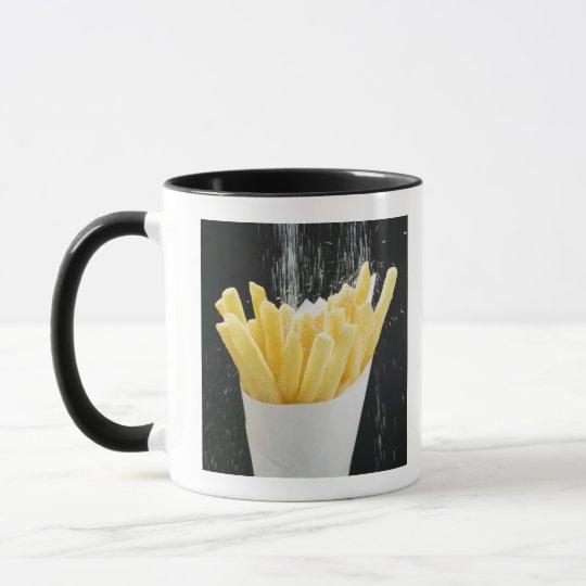Sprinkling salt on chips in paper cone mug