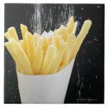 Sprinkling salt on chips in paper cone tiles