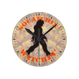 Squatchin que mira dos reloj redondo mediano