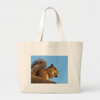 Squirrel Eating in a Tree Against Clear Blue Sky Large Tote Bag